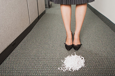 Businesswoman stood in front of pile of paper shreddings Stock Photo
