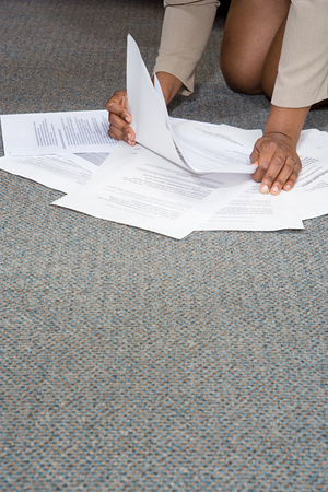 hard day at the office: Woman with paperwork on the floor