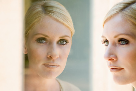 self conceit: Woman and her reflection Stock Photo
