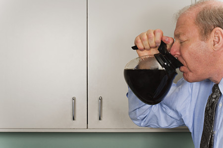 hombre tomando cafe: Businessman drinking out of coffee pot Foto de archivo