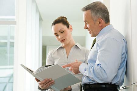 personas leyendo: Dos colegas de negocios la lectura de un documento Foto de archivo