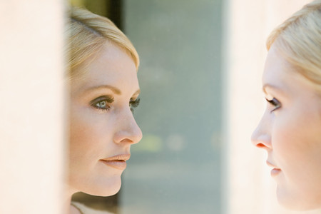 reflection: Woman looking at her reflection Stock Photo