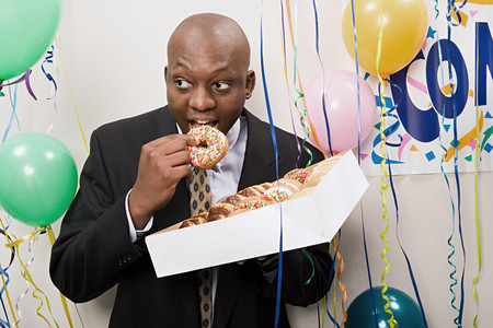 african ethnicity: Businessman secretly eating doughnuts
