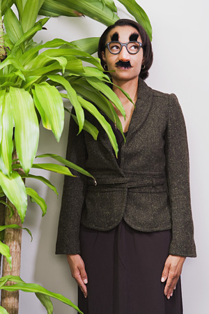 african mask: Businesswoman hiding behind plant wearing disguise
