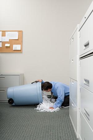 figuring: Man looking a shredded paper bin