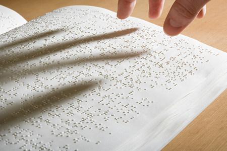 braile: Los dedos por encima de un libro en braille