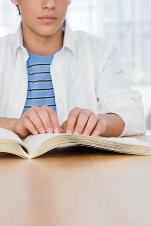 braille: Blind boy reading a braille book