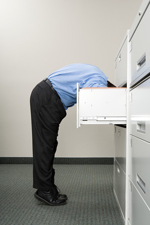office cabinet: Man looking in filing cabinet Stock Photo