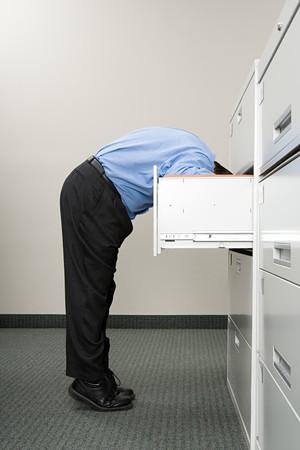 Man op zoek in archiefkast
