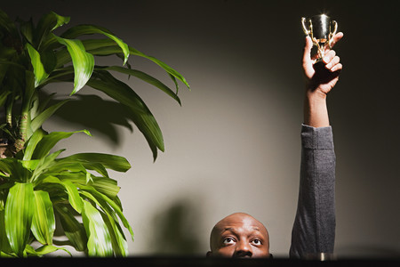 Businessman holding up his trophy