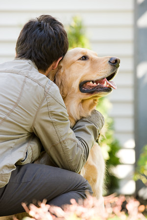 16 17 years: Teenage boy hugging pet dog Stock Photo