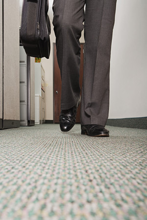 office documents: Businessman walking along corridor