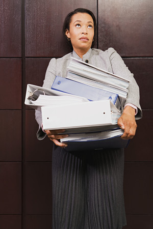 individually: Businesswoman struggling with heavy files Stock Photo