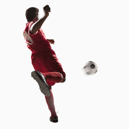 kicking: Soccer player kicking soccer ball