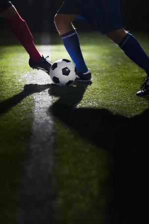 kicking: Two soccer players kicking a soccer ball