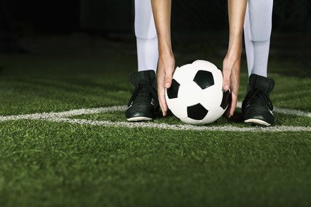 by placing: Athlete placing soccer ball for corner kick