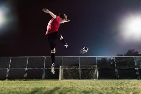 kicking: Athlete kicking soccer ball towards goal