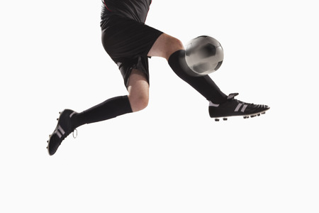 kicking: Athlete kicking soccer ball LANG_EVOIMAGES