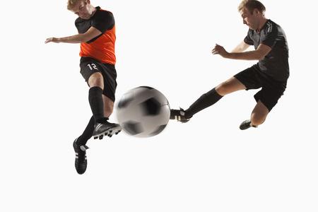sportsmanship: Two soccer players kicking a soccer ball