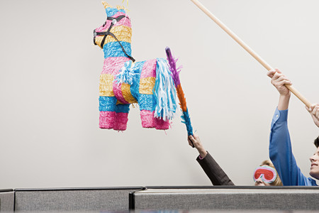 Office workers playing with a pinata