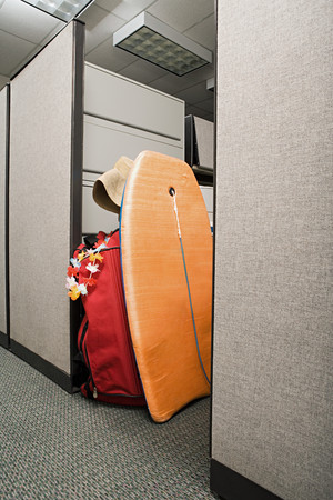 office cubicle: Suitcase and body board in office cubicle Stock Photo