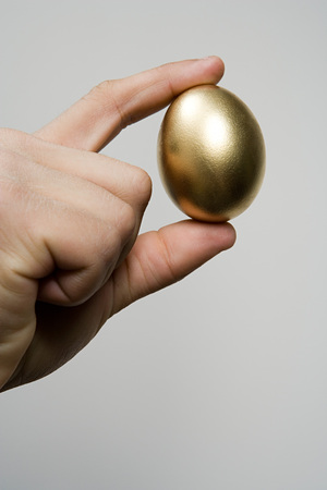 unrecognisable person: Hand holding a golden egg