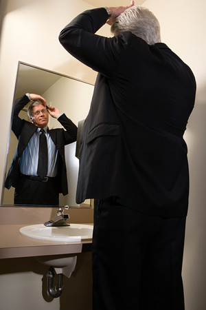 Man combing his hair in mirror Stock Photo