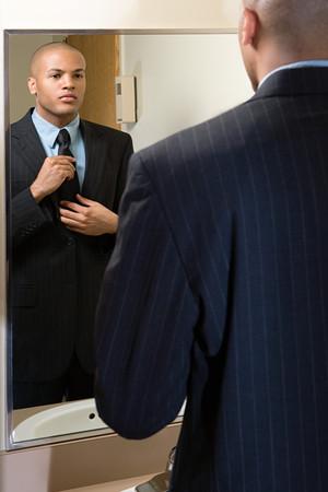 鏡でネクタイを調整する男