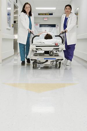 Doctors pushing patient in bed through corridor Фото со стока