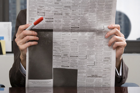image source: Person looking at newspaper Stock Photo