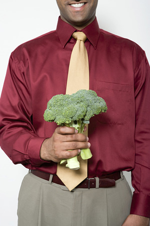 image source: Man holding a bunch of broccoli