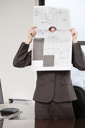 broadsheet newspaper: Woman smiling through hole in newspaper Stock Photo