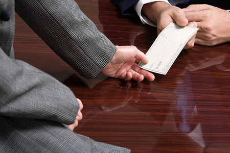 Businessman and businesswoman with blank cheque