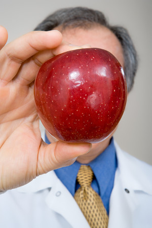 concealment: Dentist holding apple Stock Photo
