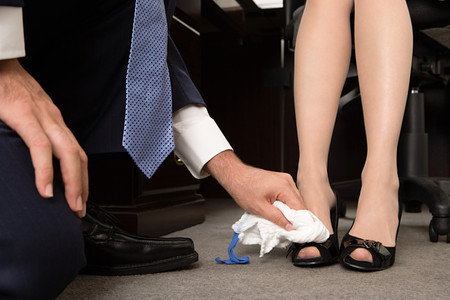 Man polishing businesswomans shoes