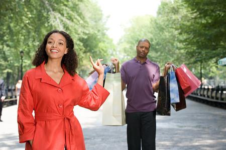 A man holding shopping bags for a woman Фото со стока