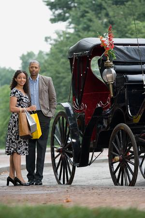 A happy couple standing next to a horse carriage Фото со стока