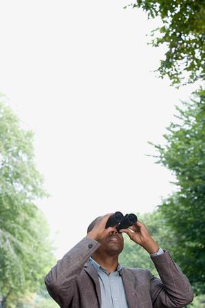 looking through an object: Man looking through binoculars