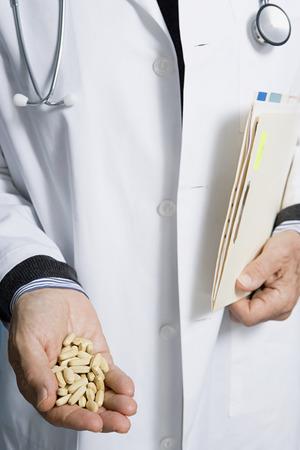 錠剤やドキュメントを保持している医師