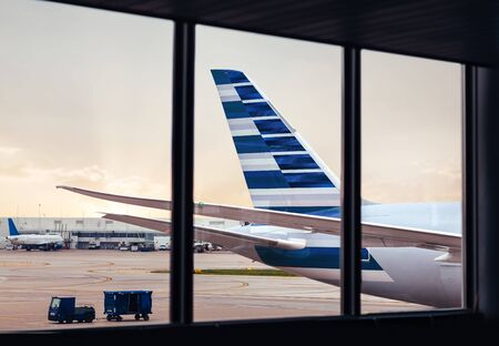 View of airplane fuselage tail through window at airport