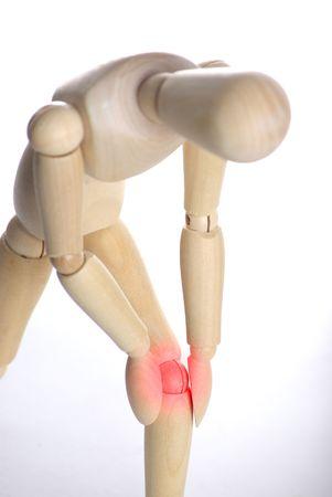marioneta de madera: Concepto de dolor - persona que ostente su rodilla