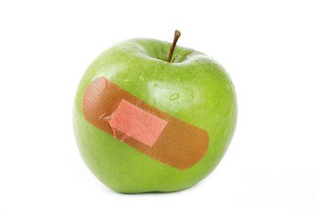 Una mela verde con una banda di aiuto su di esso.  Archivio Fotografico