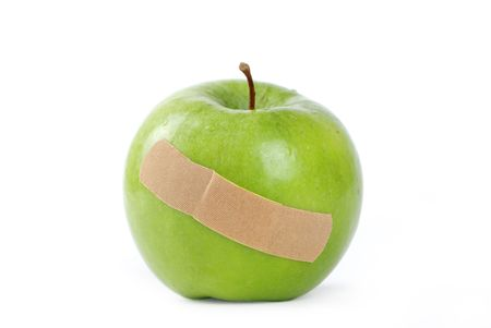 A Green apple with a band-aid on it.  Stock Photo