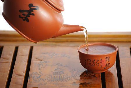 Pouring tea into tea cups photo