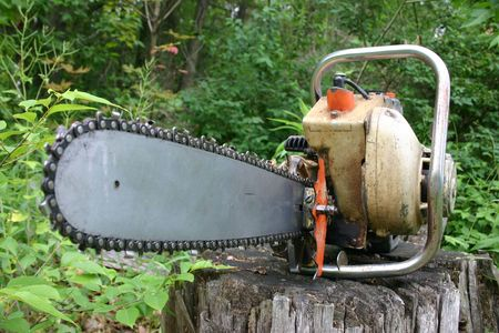 A vintage chainsaw on a stump