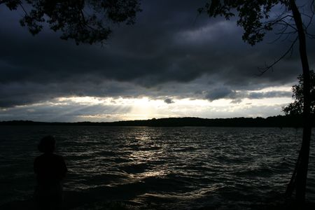 sihlouette: Sihlouette of a woman watching a storm over a lake