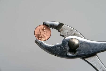 A penny held by a pliers indicating financial squeeze