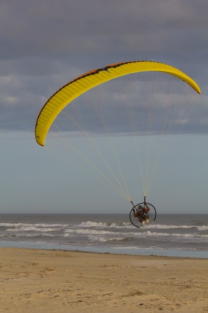 Galveston Island, TX - January 6, 2012 : A powered paraglider taking off from a beach