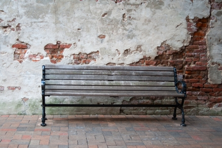 An old empty bench in front of a crumbling wall