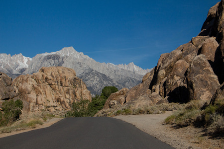 A road through the Alabama Hills with the Sierra Nevada mountain range including Mt. Whitney in the background